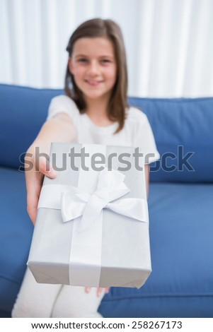 Little girl offering a silver gift at home in the living room - stock photo