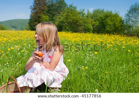 Little girl on a beautiful sunlit meadow in spring on an Easter egg hunt having just found a nest - stock photo