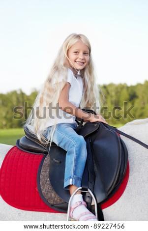 Little girl on a horse - stock photo