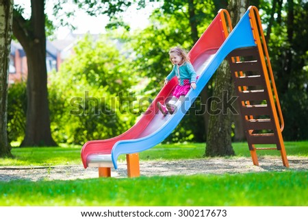 Little girl on a playground. Child playing outdoors in summer. Kids play on school yard. Happy kid in kindergarten or preschool. Children having fun at daycare play ground. Toddler on a slide. - stock photo