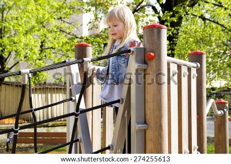 little girl on outdoor playground equipment - stock photo