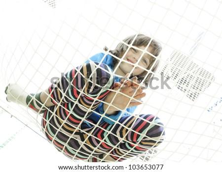 little girl on playground climbing in net - stock photo