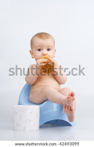 Little girl on potty with bottle teas and lavatory paper,on white background. - stock photo