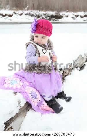 Little girl on snowy beach - stock photo