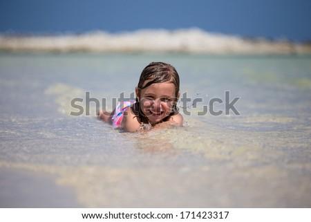 Little girl on the beach on a sunny day - stock photo