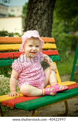 little girl on the bench in park - stock photo