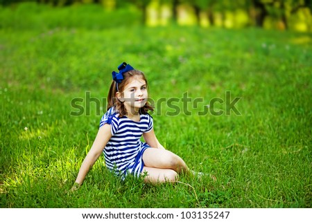 Little girl on the grass - stock photo