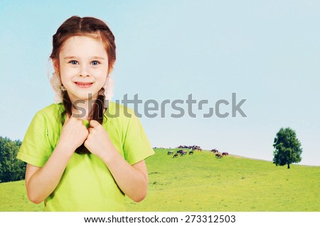 Little girl on the green hills in sunny day - stock photo