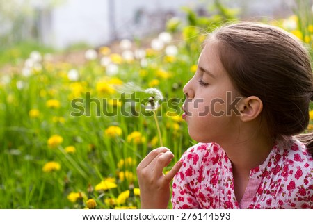 little girl on the meadow in  spring day - blowing dandelion - stock photo