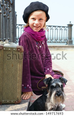 Little girl on the road with his dog and suitcase - stock photo