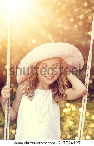 Little girl on the swing - stock photo