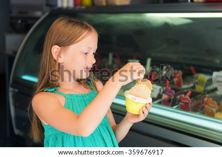 Little girl on vacation, kid girl buying ice cream in the shop - stock photo