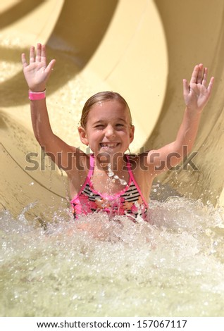 little girl on water slide during vacation - stock photo