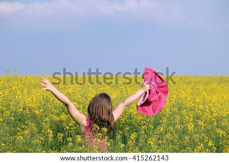 Little girl on yellow flower field summer season - stock photo