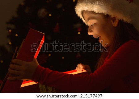 Little girl opening a magical christmas gift at home in the living room - stock photo