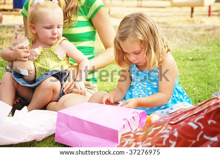 Little girl opens a present at her birthday party - stock photo