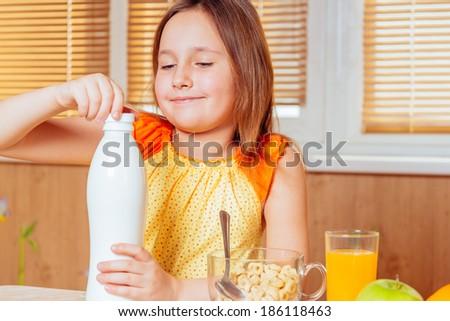 Little girl opens bottle of milk for cereal flakes - stock photo