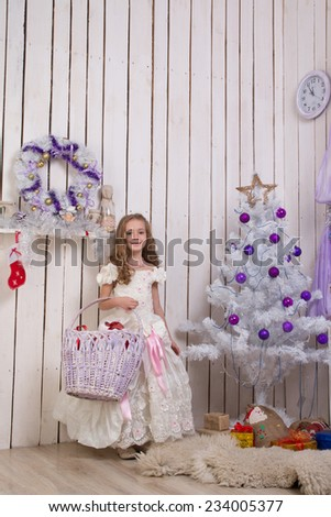 Little girl over christmas fir tree with wicker basket of presents, focus on girl - stock photo