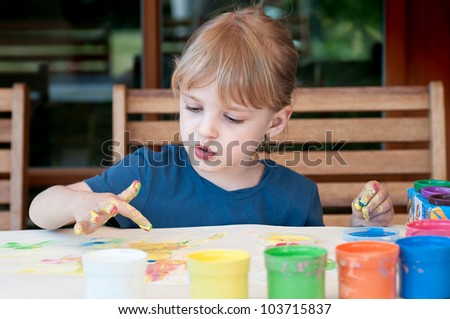 Little girl painting colors on hand - stock photo
