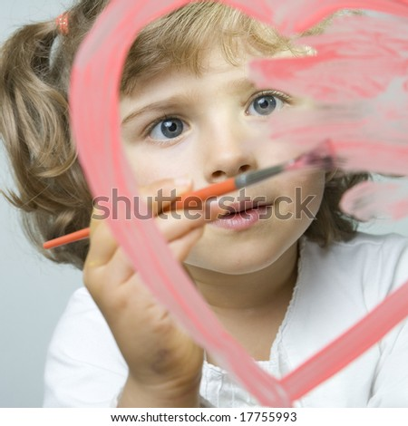 Little girl painting on glass - stock photo