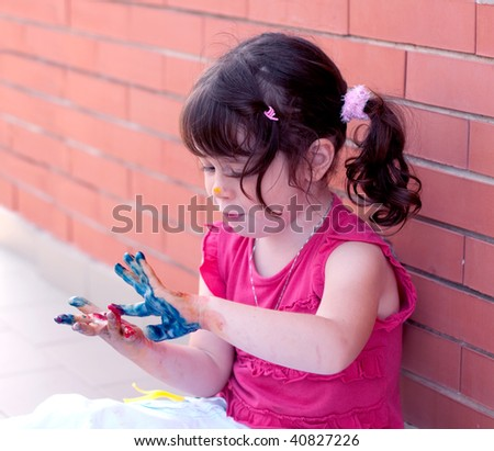 Little girl painting on her hand - stock photo
