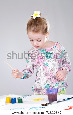 Little girl painting with brush - stock photo