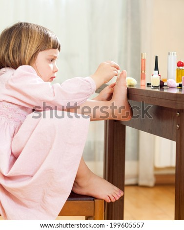 Little girl paints her nails on  feet - stock photo