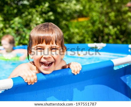 Little girl palying in a swimming pool at a summer garden - stock photo
