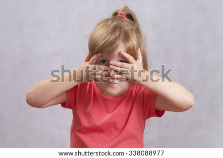 Little girl peeping through hand with one eye isolated over white background - stock photo