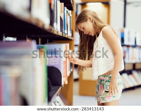 Little girl picking a book in public library - stock photo
