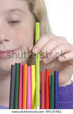 Little girl picking a crayon detail. - stock photo