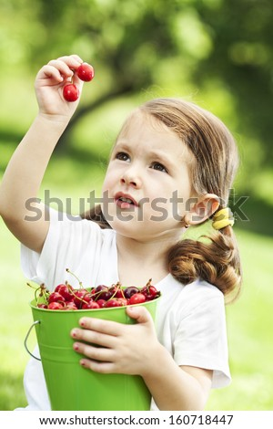 Little girl picking cherry from a tree - stock photo