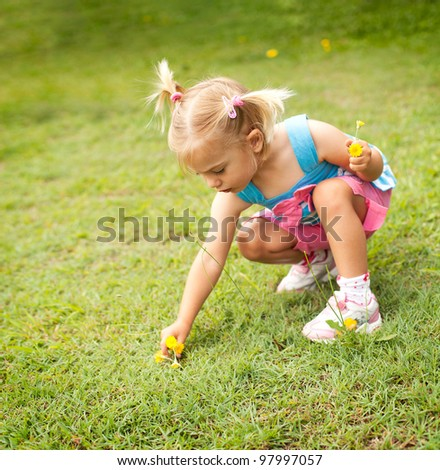 Little girl picking some yellow flowers in the garden - stock photo