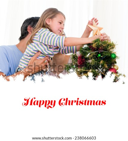 Little girl placing a star in a Christmas tree against happy christmas - stock photo