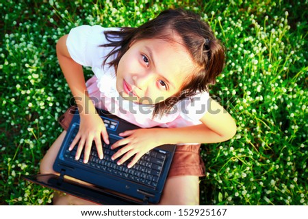 little girl play computer  on green grass - stock photo