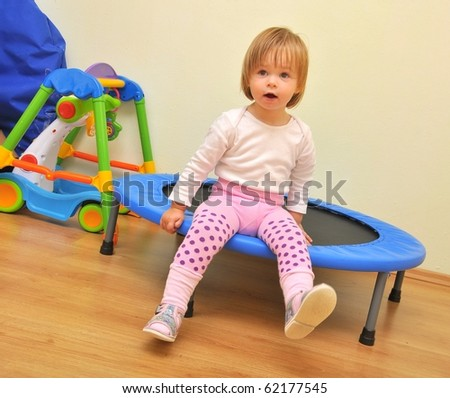 little girl play on a trampoline - stock photo