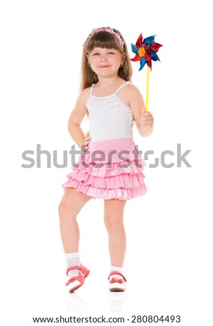 Little girl play with pinwheel toy windmill, isolated on white  - stock photo