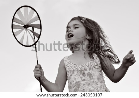 Little girl play with pinwheel  toy windmill outdoors. concept photo seasonal and weather. (BW) - stock photo