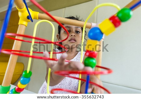 Little girl play with the wooden bead wire - stock photo