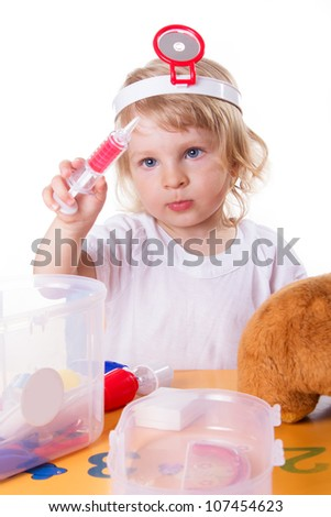 Little girl playing as doctor with syringe on white - stock photo