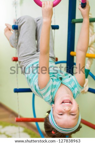 little girl playing at gymnastic rings - stock photo
