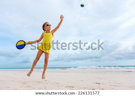 Little girl playing beach tennis on vacation - stock photo
