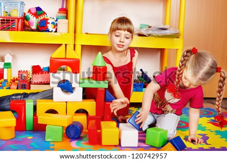 Little girl playing block and construction set in preschool. - stock photo