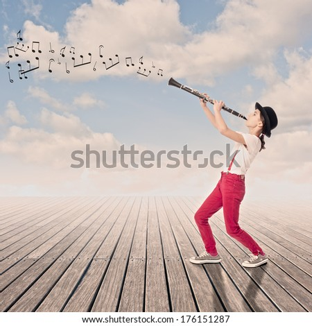 little girl playing clarinet on a wharf - stock photo
