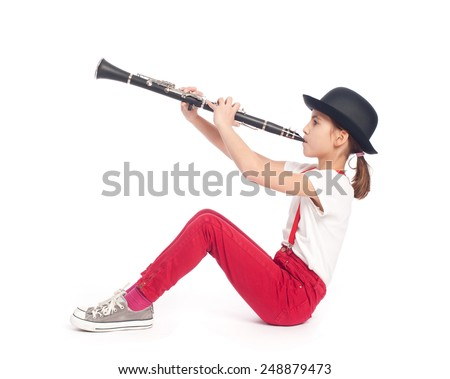 little girl playing clarinet on a white background - stock photo