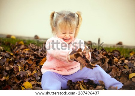 Little girl playing in autumn leaves - stock photo