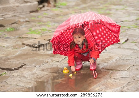 Little girl,playing in muddy puddles in the park, rubber ducks in the puddle - stock photo