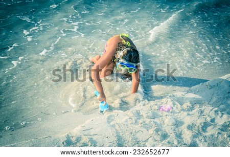 little girl playing in sand on the beach near the ocean - stock photo