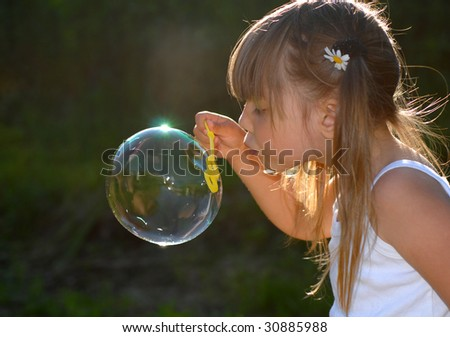 Little girl playing in the garden - stock photo