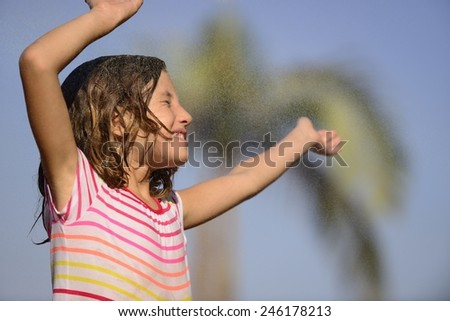 little girl playing in the summer rain - stock photo